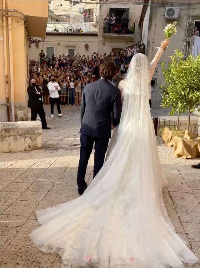 Los recién casados inmediatamente después del 'sí' saludan a la nutrida multitud de espectadores que se congregaron frente al Santuario de Santia Maria la Nova en Scicli, en la provincia de Ragusa