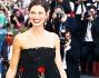 Bianca Balti bellissima in abito lungo nero con fiori rossi a dare un tocco di colore al suo look