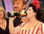 Alla goccia la bottiglia di champagne per Marisa Laurito osservata con stupore da Gigi Proietti