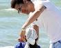 Eddy Martens in spiaggia con la piccola Maelle che si protegge dal sole con una lunga bandana in testa